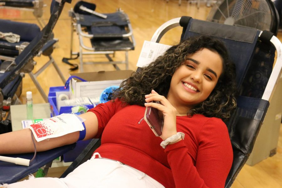 Senior+Jaelen+Lopez+smiles+while+donating+blood+during+the+fourth+annual+blood+drive+held+in+the+auxiliary+gym+Sept.+11