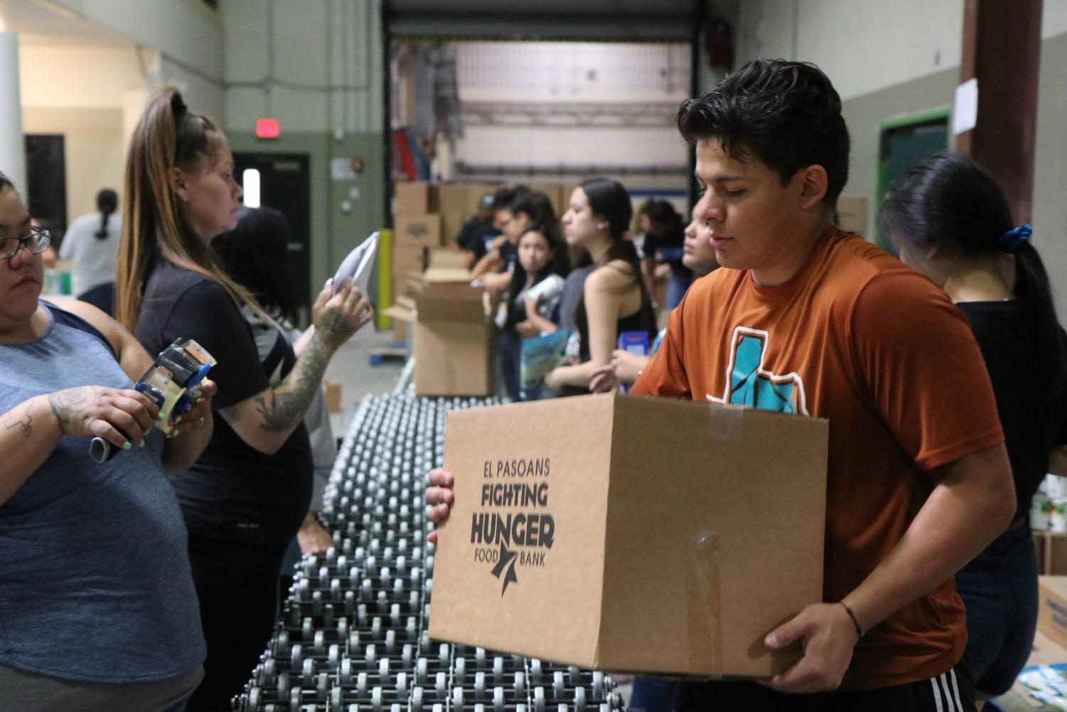 Junior Victor Nevarez carries a box filled with food Saturday morning Aug. 16 at the El Pasoans Fighting Hunger Food Bank.